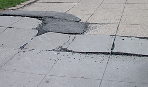 Photo of a sidewalk with broken pavement, raised sections, and patches