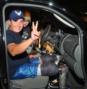 Photo:  Inside a van with the door open, a man wearing ball cap and shorts smiles and makes a victory sign.  He has two prosthetic legs.