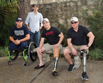Photo:  Three seated men pose for the camera:  two of them sit on a bench and have prosthetic legs; one sits in a wheelchair and has double leg amputations.  A fourth man stands behind the group.