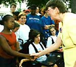 Janet Reno shakes hands with girl
