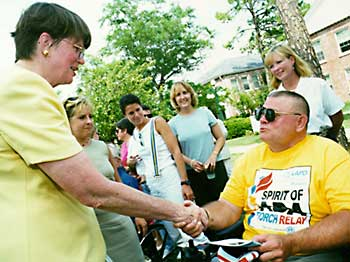 Janet Reno shakes hand with man using a wheelchair
