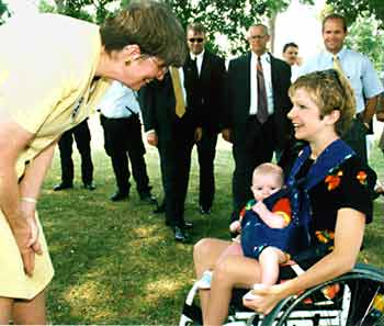 Janet Reno speaks to mother using a wheelchair and her baby