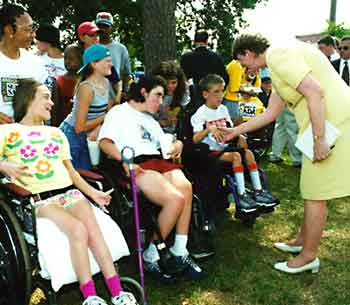 Janet Reno shakes hands with children who use wheelchairs
