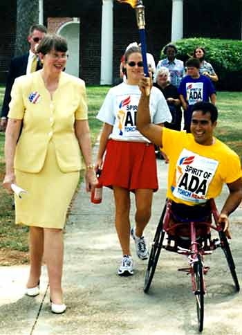 Janet Reno walks with torch carrier
