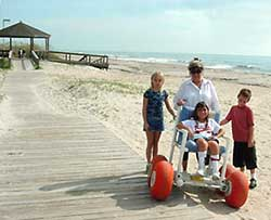 photo - family on beach with girl in beach wheelchair