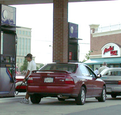 a person is putting fuel into their automoble at a fuel pump