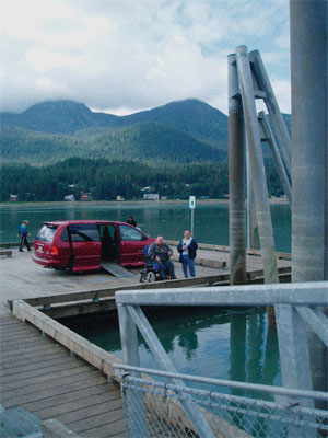 A picture of two men one in a wheelchair fishing on an accessible pier in Alaska.