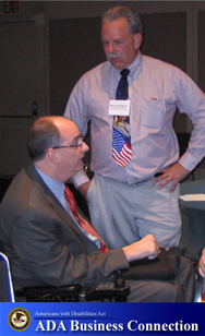 Photo: A man is having a conversation with a man using a wheelchair; ADA Business Connection Logo