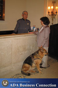 Photo: A woman with a service animal is at a hotel check-in counter; ADA Business Connection Logo