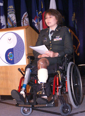 Photo: Assistant Secretary Duckworth, who sits in a wheelchair alongside a podium, has two prosthetic legs.