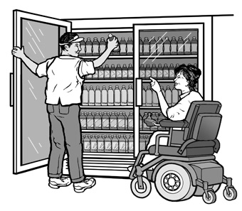 A convenience store employee reaches for a bottle of juice from the top rack of a drink cooler for a woman using a power wheelchair.